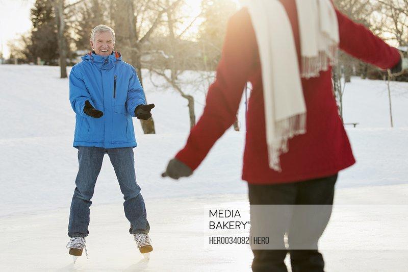 Playful senior couple ice skating