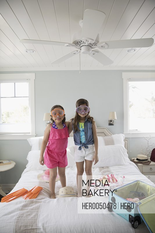 Portrait Latina sisters packing for vacation wearing goggles on bed