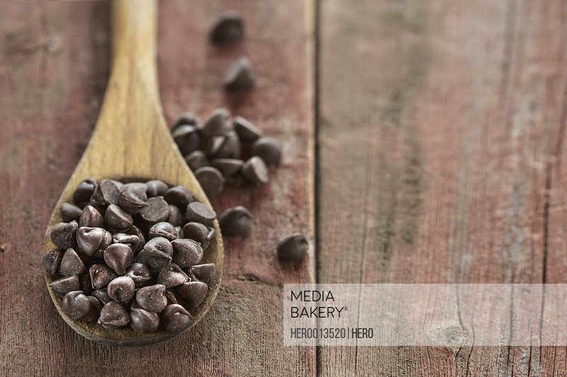 Chocolate chips in wooden spoon on wood table