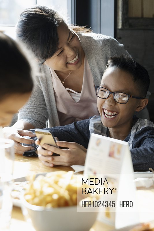 Happy, laughing family with smart phone dining at restaurant table