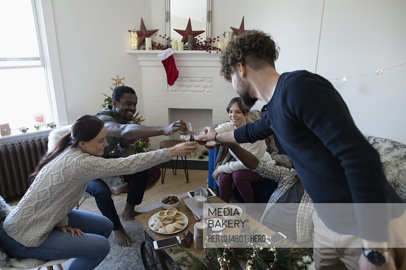 Millennial friends toasting wine glasses in Christmas living room