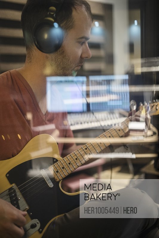 Focused male guitarist with headphones playing in recording studio
