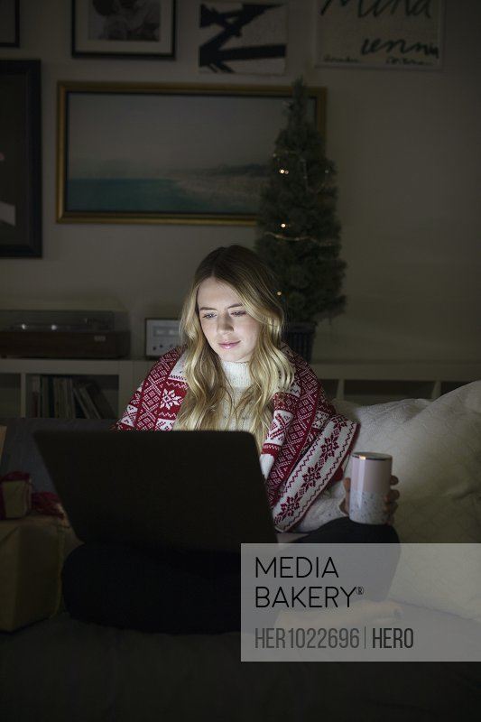 Young woman using laptop in dark Christmas living room