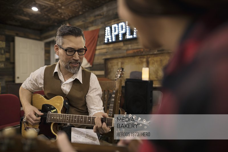 Male singer-songwriter musician playing guitar and writing music on stage
