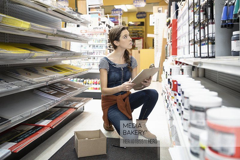 Female business owner with clipboard checking inventory in art supply shop