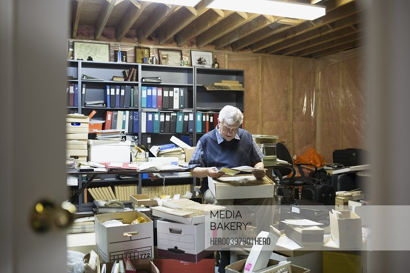 Senior man reading old letters in boxes
