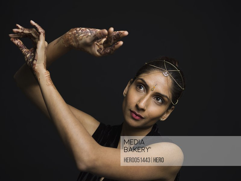 Serious Indian woman with bindi and Henna tattoos dancing against black background