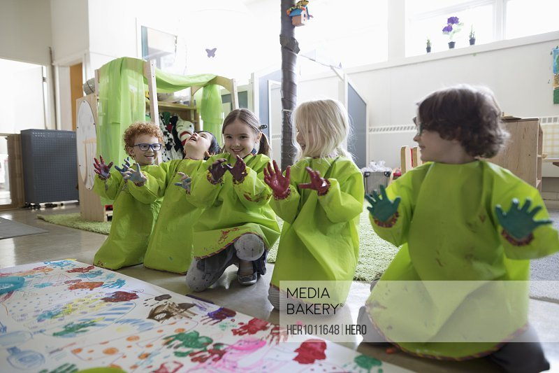 Playful preschool students in smocks showing finger paint on hands at poster in classroom