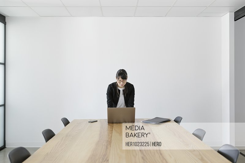 Businesswoman preparing, working at laptop in conference room