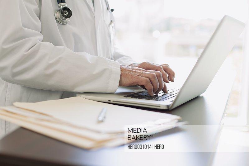 doctor keyboarding on laptop