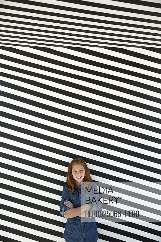 Portrait girl against black and white striped wall