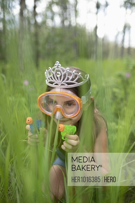 Playful girl in tiara and goggles crouching in tall grass with squirt guns