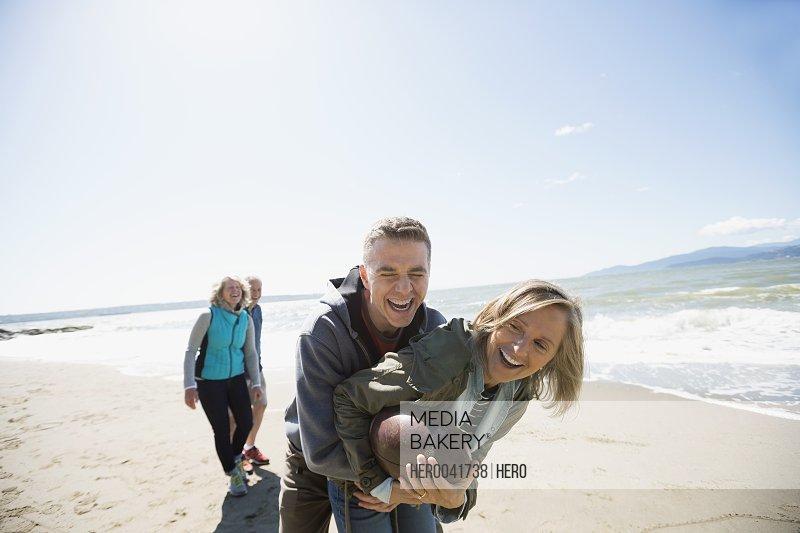 Playful couple playing football on sunny beach