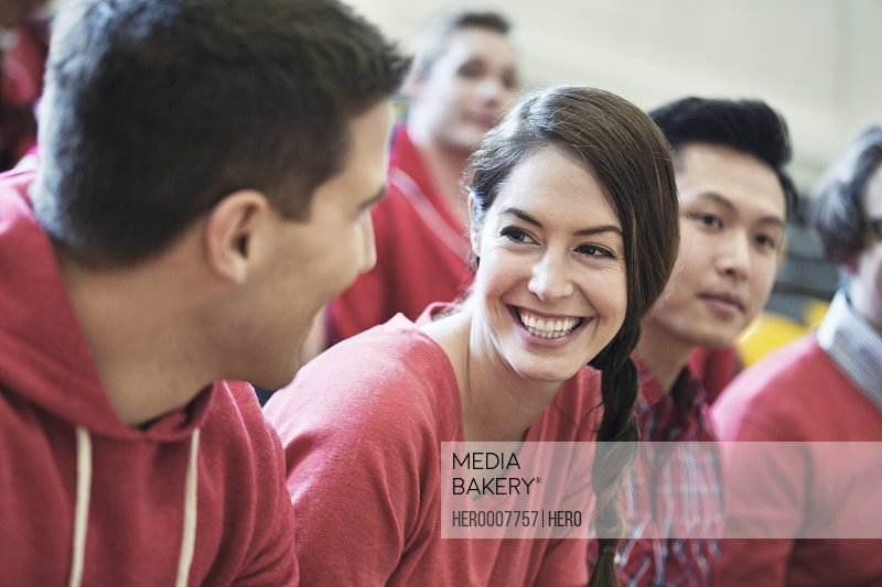 Female student looking at male friend at college sporting event