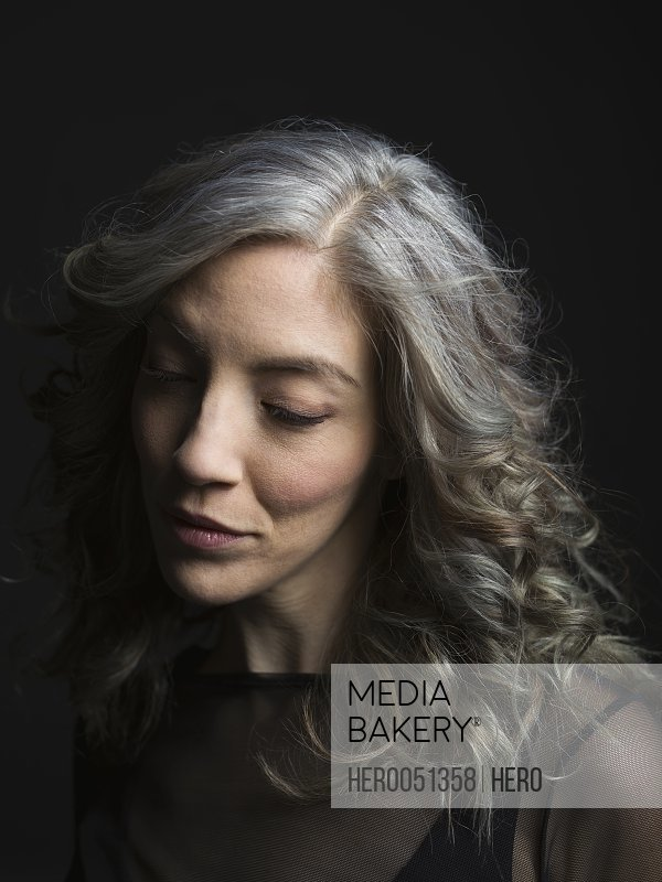 Serious pensive woman with gray hair looking down against black background