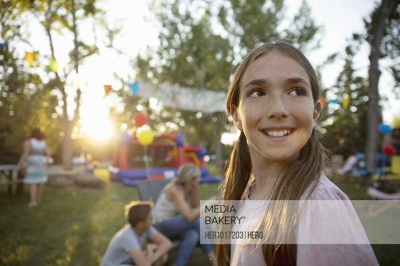 Portrait smiling girl looking over shoulder at summer neighborhood block party in park