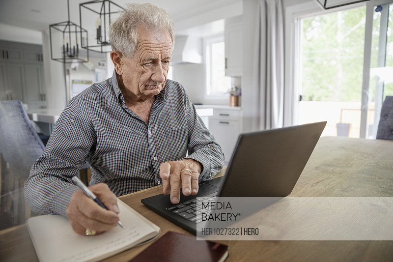 Senior man with notebook using laptop at dining table