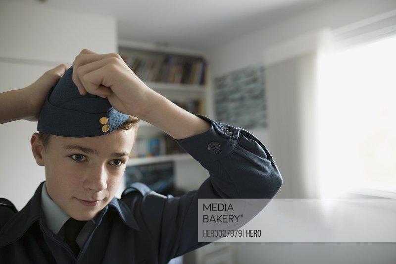 Boy putting on cadet uniform hat