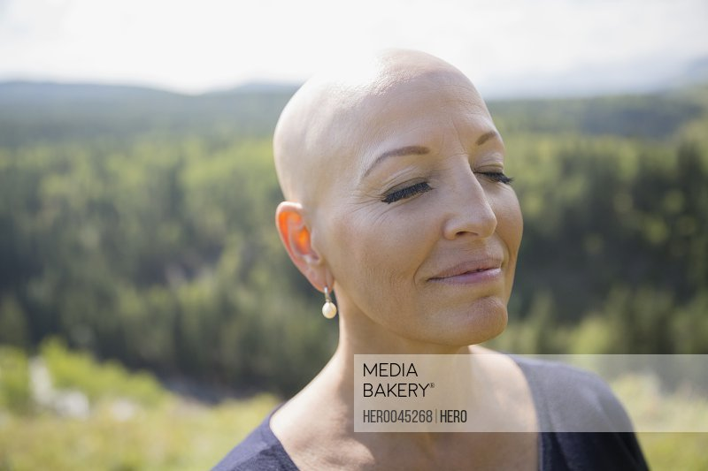 Close up serene female cancer survivor with shaved head and eyes closed