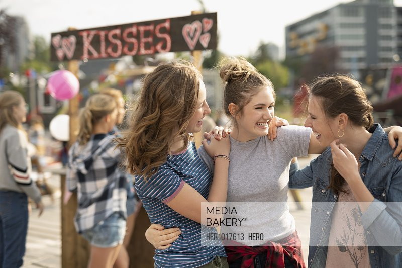 Teenage girls bonding at kissing booth in park