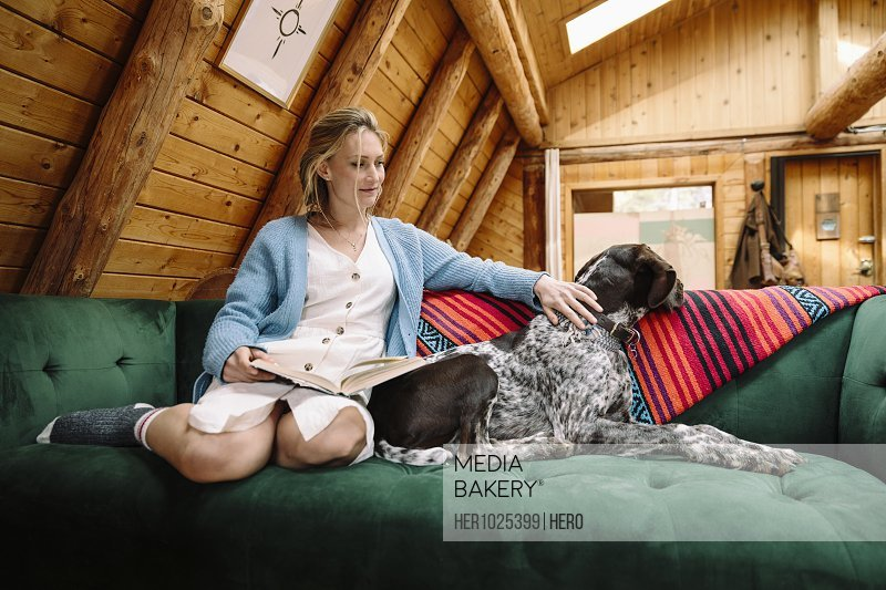 Woman with dog reading book, relaxing on cabin sofa