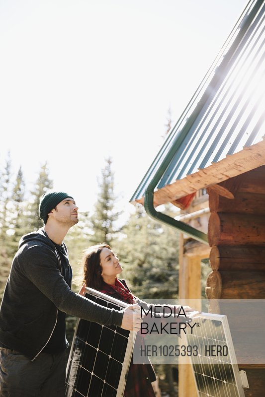 Couple installing solar panels on cabin