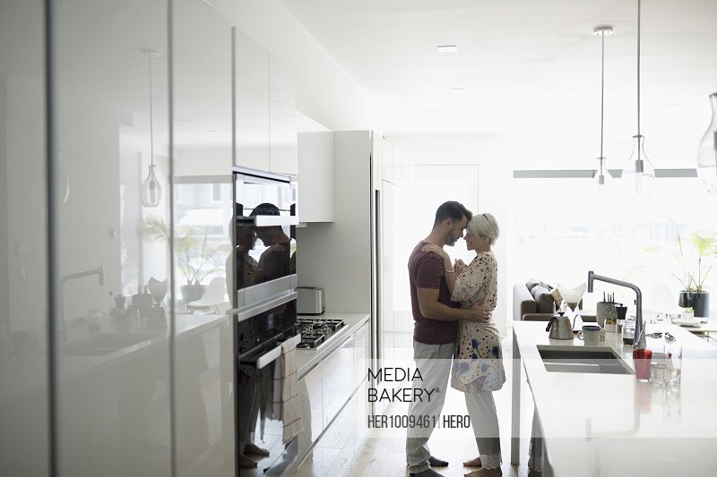 Affectionate, romantic couple hugging in morning kitchen