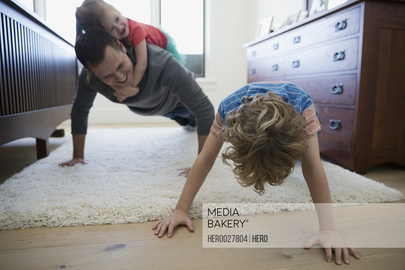 Father and son doing push-ups bedroom rug