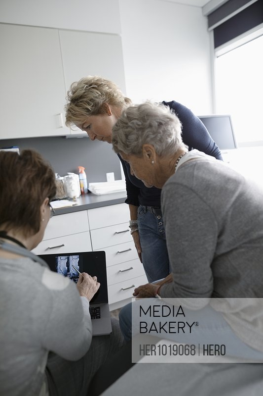 Female nurse showing x-ray on laptop to senior patient and daughter in clinic examination room