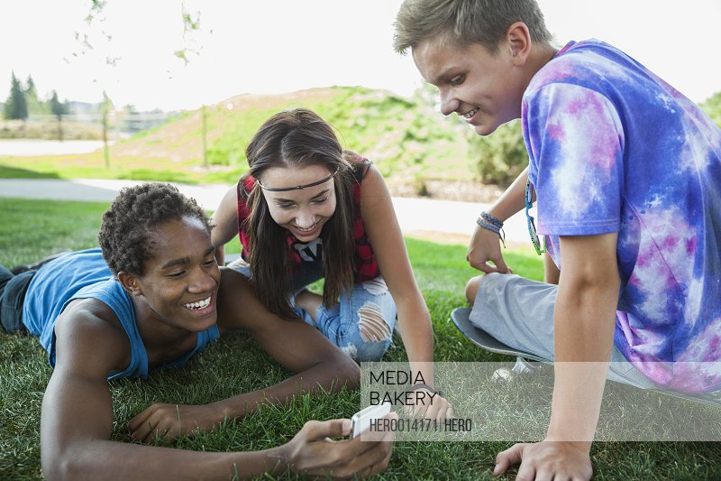 Teenagers using cell phone in grass