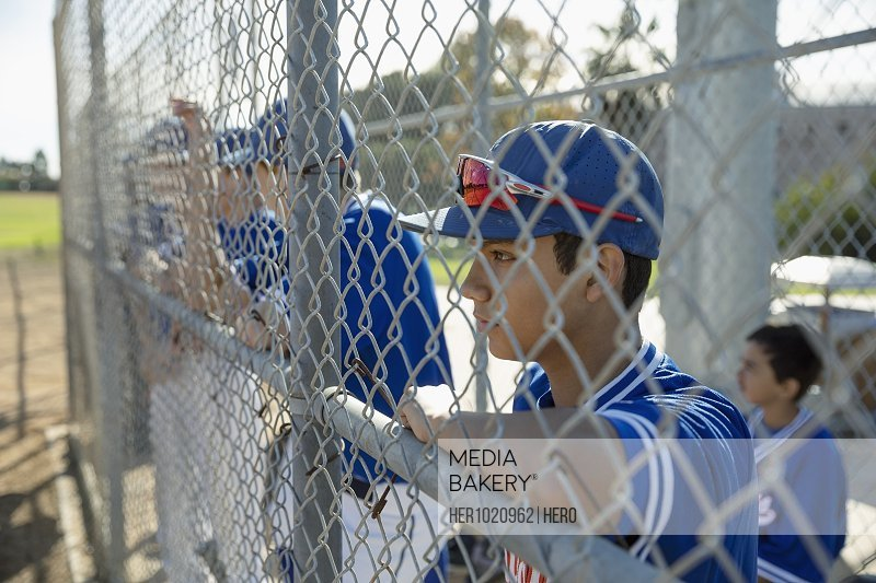Focused baseball player watching game behind fence