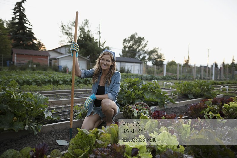 Portrait smiling woman tending to vegetable garden