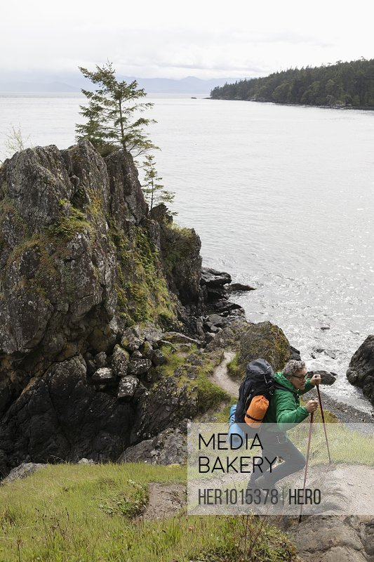 Active senior man backpacking on cliff overlooking ocean