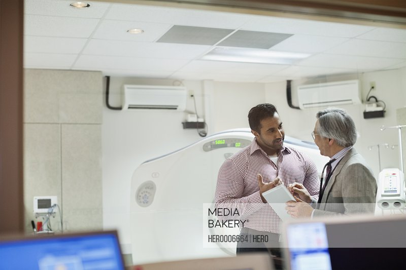 Senior doctor discussing with male patient in examination room