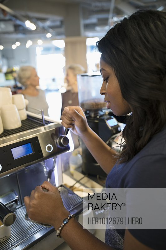 Female barista working at espresso machine in cafe