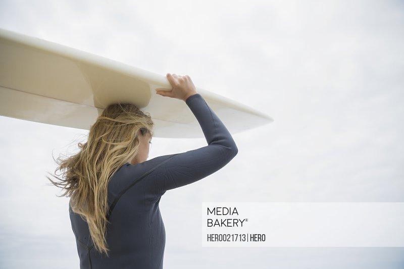 Blonde female surfer carrying surfboard overhead
