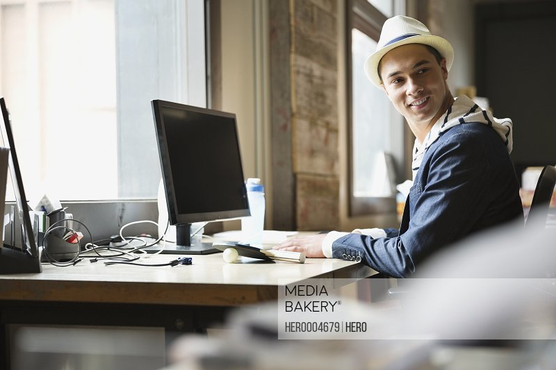 Smiling entrepreneur sitting at desk in creative office space