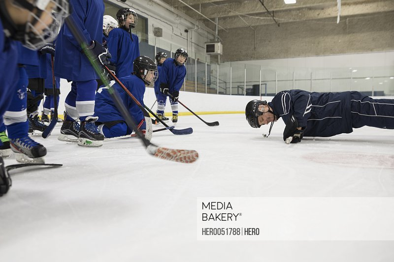 Boy ice hockey players watching coach at practice on ice hockey rink