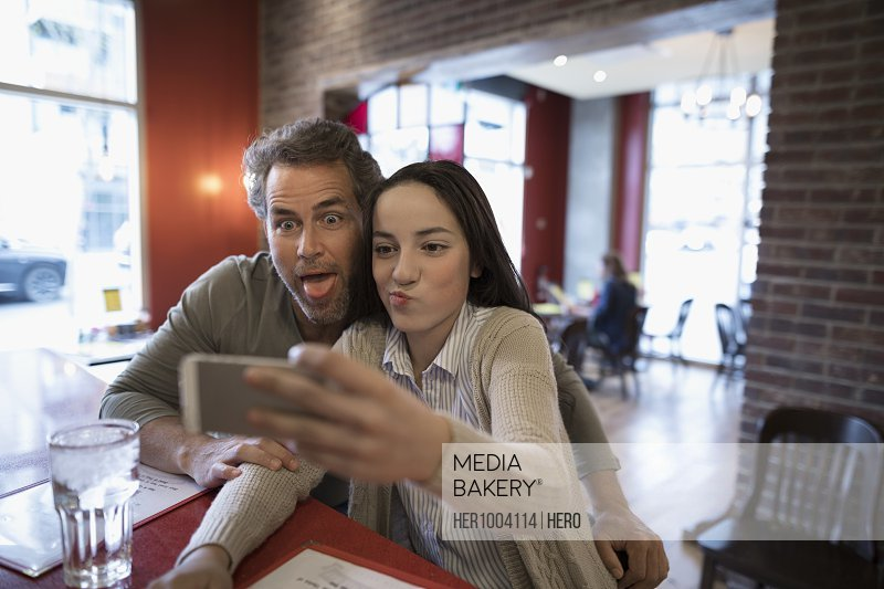 Father and teenage daughter taking selfie at diner counter