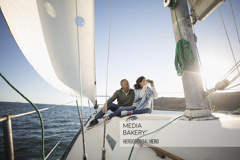 Mature couple using camera on sunny sailboat