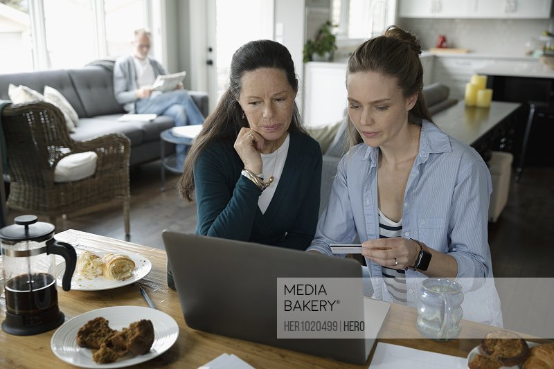 Mother and adult daughter online shopping at laptop