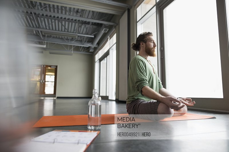 Serene man meditating in lotus position on yoga mat in gym studio