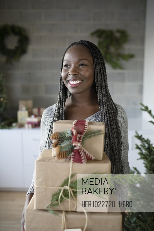 Happy young African American woman holding stack of Christmas gifts