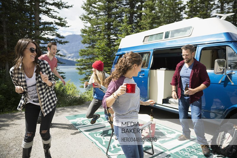 Playful friends dancing and drinking outside camper van at remote lakeside