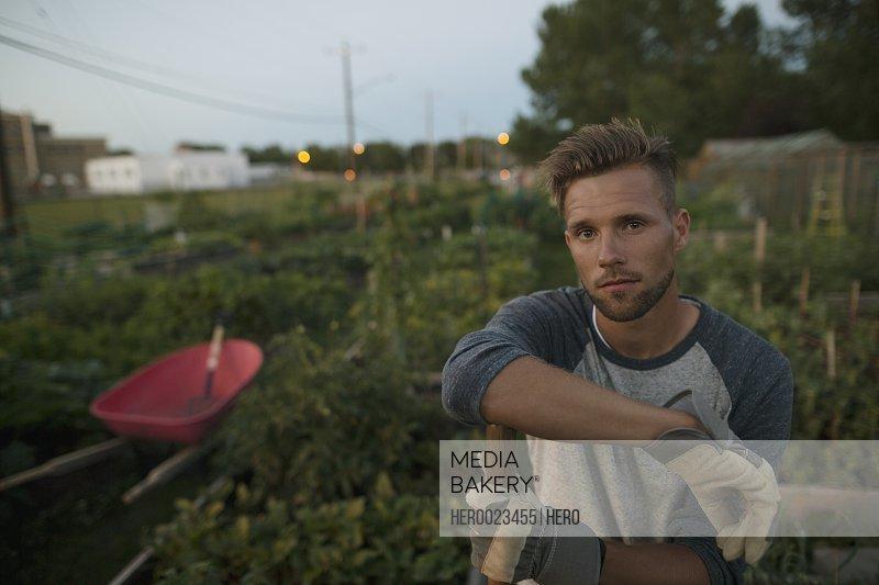 Portrait confident man in vegetable garden at dusk