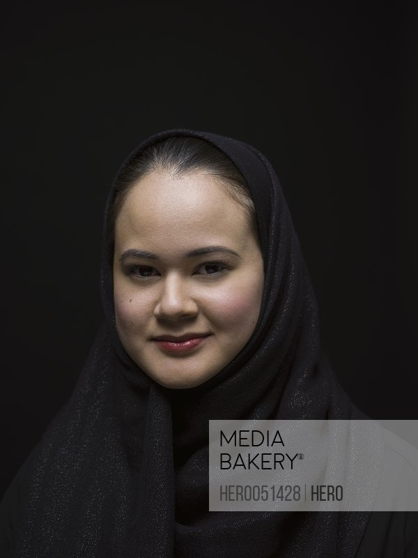 Portrait smiling Middle Eastern woman wearing black hijab against black background