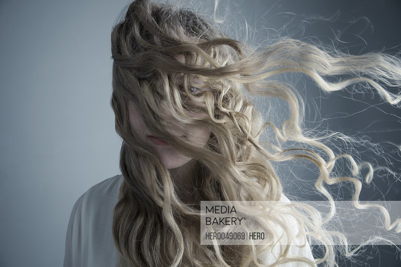 Portrait wind blowing long curly blonde hair across face of Caucasian young woman