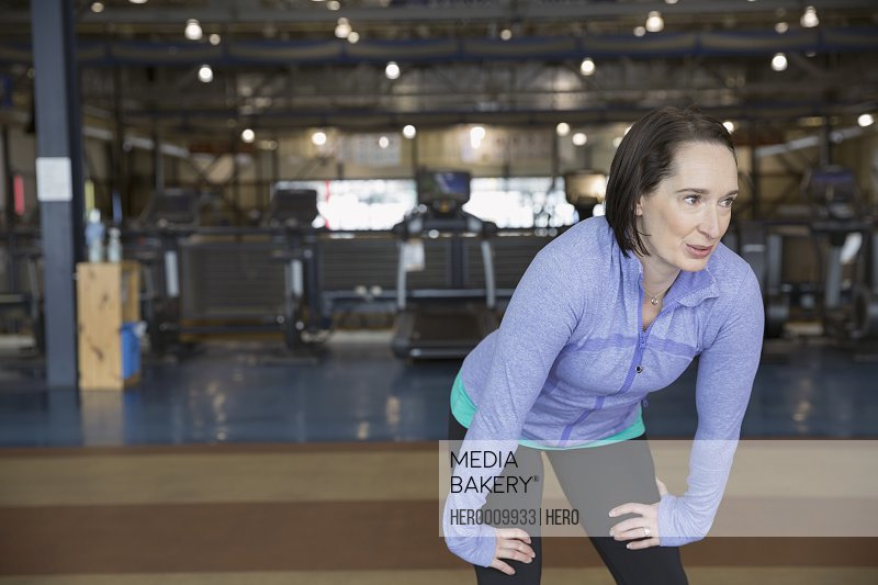 Woman resting hands on knees at gym