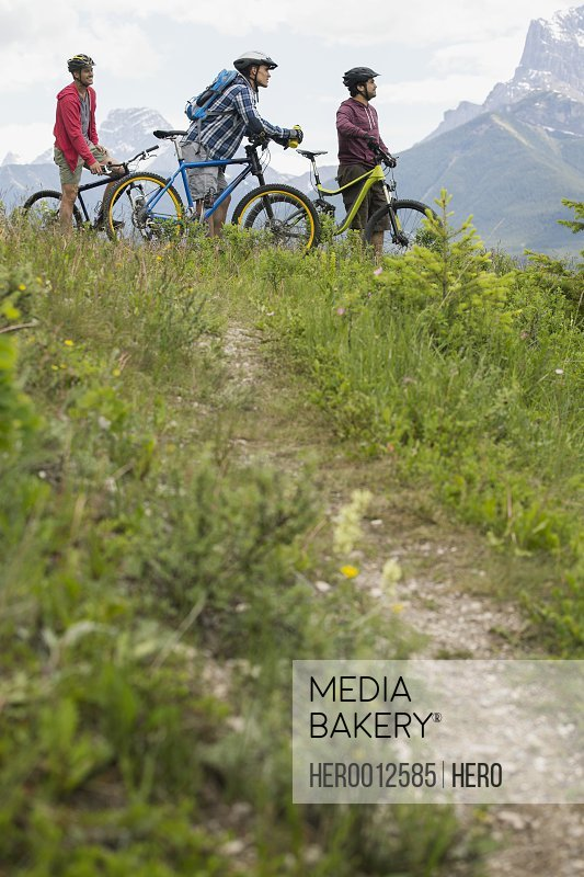 Men on mountain bikes in grass below mountain