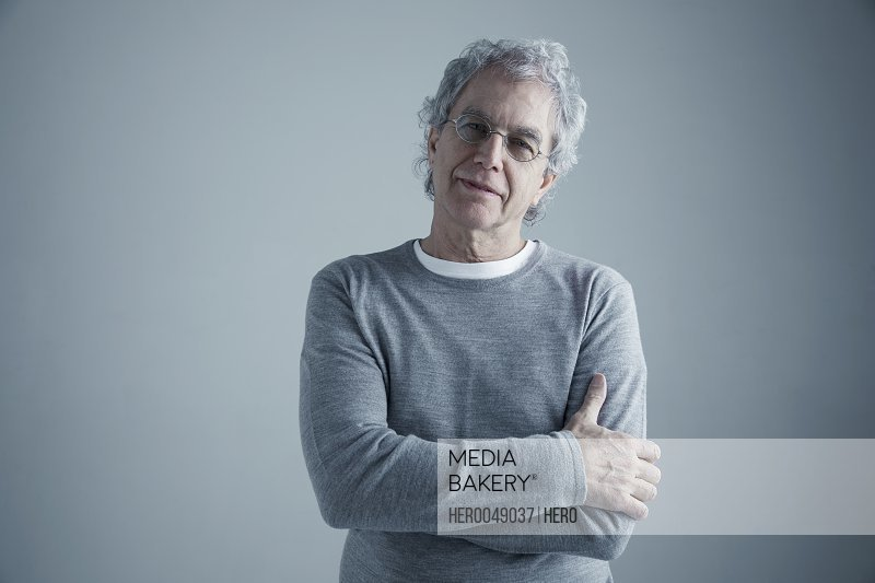 Portrait confident Caucasian senior man with gray hair and eyeglasses with arms crossed